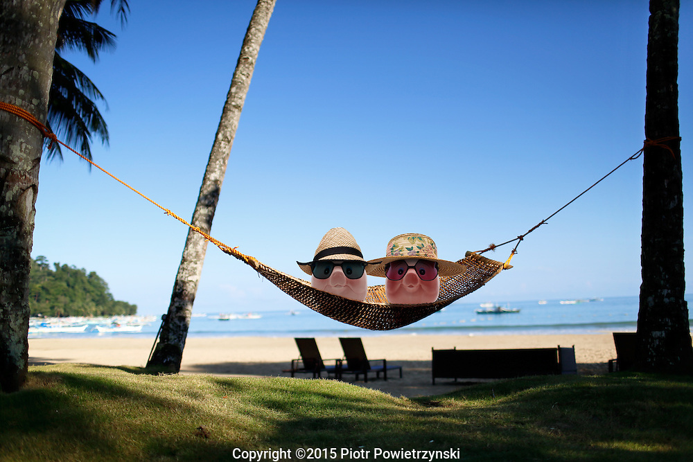 Piggy banks couple in hammock on beach. Palawan, Philippines, Asia.