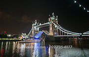 A boat passes under the Tower Bridge at night in London, England.