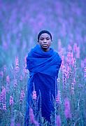 Woman in field with blue cloth, blue light with purple flowers
