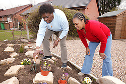 Elderly woman in garden with carer,