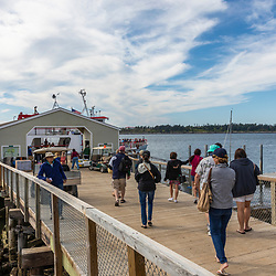 Passengers board a Maine State Ferry at the dock on Cliff Island in Casco Bay, Portland, Maine.