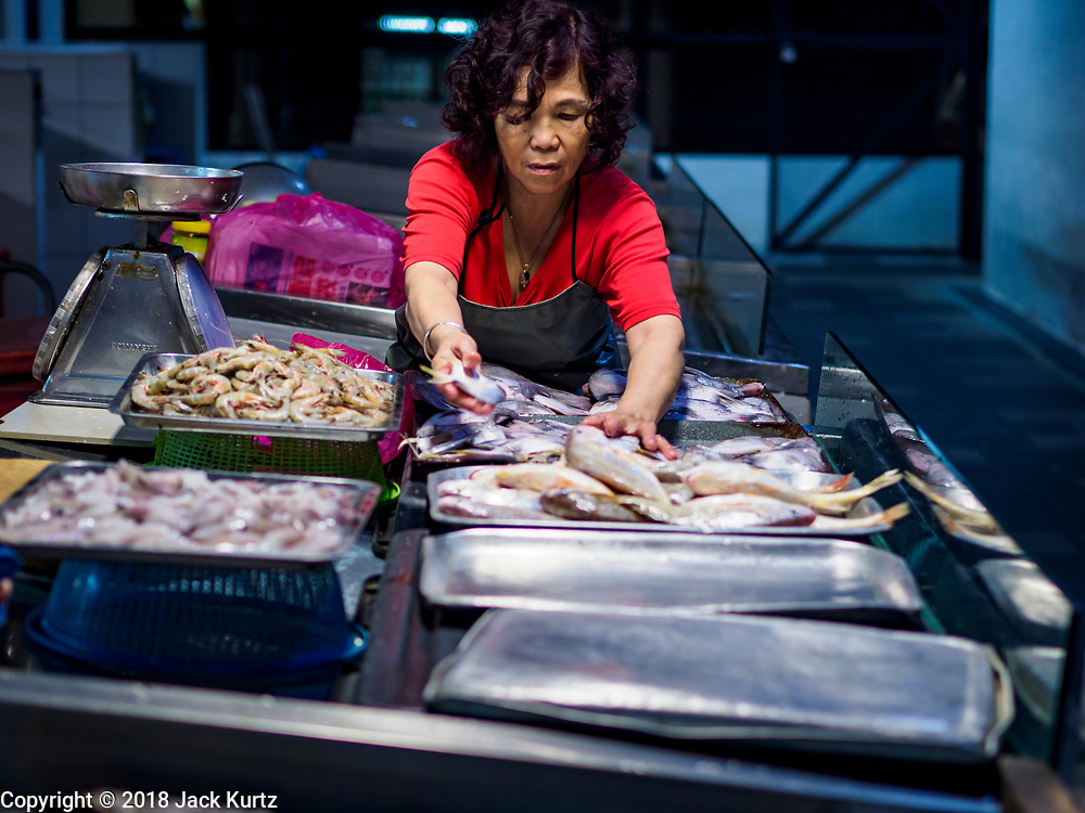 24 AUGUST 2018 - GEORGE TOWN, PENANG, MALAYSIA: A market vender sets out fish to sell in Chowrasta Market in central George Town. Chowrasta Market was originally built in 1890 and is the older of two traditional markets in George Town. The original building was torn down and replaced with a modern building in 1961 and has been renovated several times since.     PHOTO BY JACK KURTZ