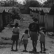 Lesama and several Maleku children walk through the main housing area on the reservation.