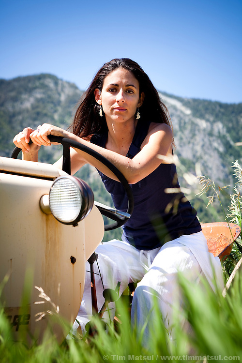 A beautiful,  young Latina woman sits on an old tractor in a rural grass field on a sunny day.