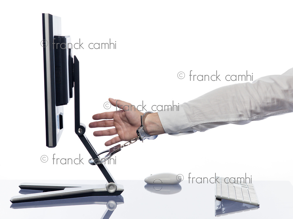hand chained to computer with handcuffs expressing addiction  concept isolated studio on white background