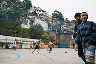 Kids play football on a concrete pitch at the Santo Amaro favela, Rio de Janeiro, Brazil. According to Patrick Ashcroft an English (Stockport) researcher and teacher who lives in the favela, it is fairly quiet and non violent. There is a heavily armed police presence in the favela.<br /> Picture by Andrew Tobin/Focus Images Ltd +44 7710 761829<br /> 20/06/2014