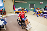 30 DECEMBER 2009 -- PHOENIX, AZ:  Mackenzie Saunders (CQ) spins around in her wheelchair after physical therapy at St. Joseph's Hospital in Phoenix Wednesday. Mackenzie was knocked down by another player during a soccer game. She finished the game but later in the day her legs started hurting and her parents took her to a hospital. Three hospitals later, she was in St. Joseph's with a diagnosis of a swollen spine and she couldn't walk. Now she's in physical therapy. She is expected to make a full recovery but her doctors have said she won't be able to play soccer for at least another 16 months.       Photo by Jack Kurtz