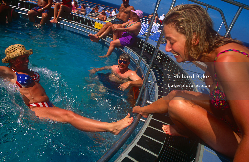 Young women at the poolside are watched by older men, on 15th May 1996, aboard the Carnival cruise ship Ecstasy, off the Gulf of Mexico, USA.