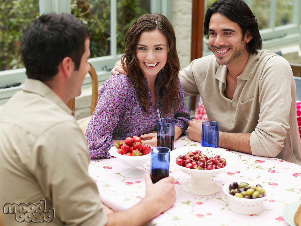 Young couple sitting at verandah table smiling to friend elevated view