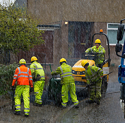 Midlothian Council have instigated repairs to the pavements in Penicuik and the changeable weather has not stopped the workers from Cummock who are involved in the process. Road teams including the likes of  Ricky Liddle, Przemyslaw Baczyk, Kev Wright, Mickey Kennedy, Jakos Targosz and Digger driver John Taylor first rip up the damanged pavement; flatten the base and reinstate with hot tar before the steam roller enures the pavement is flat and safe.<br /> <br /> (c) Ger Harley | Edinburgh Elite media 26 April 2016