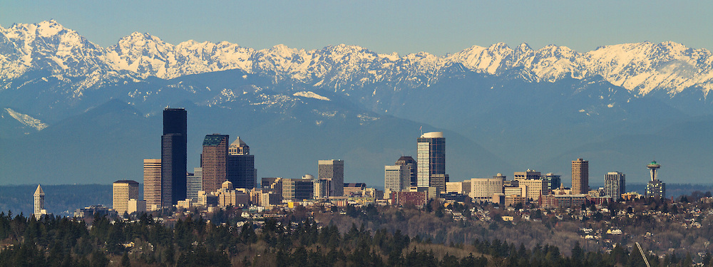 The snowy Olympic Mountains beyond the Seattle skyline on a sunny March day. (Mike Siegel / The Seattle Times)