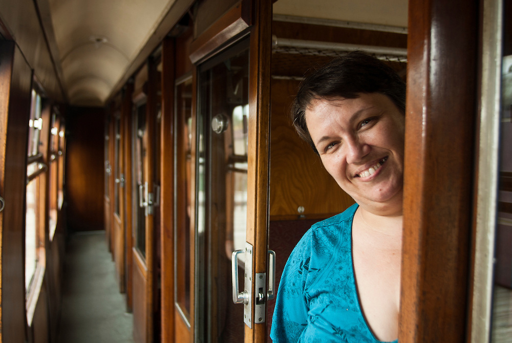 Lathan Goumas | The Bay City Times..Director of the Standish Historic Depot Sue Stein stands in a British Railway coach car built in 1954.