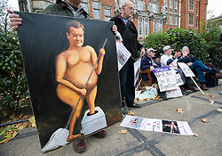 © Licensed to London News Pictures. 29/11/2011. London, UK. A man holds a satirical painting of George Osborne outside the The HOuses of Parliament next to pension campaigners today (29/11/2011) following the Chancellors Autumn statement . Photo credit : Ben Cawthra/LNP