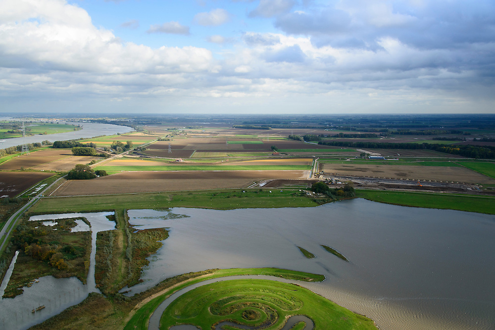 Nederland, Noord-Brabant, Werkendam, 23-10-2013; Ruimte voor de Rivier project Ontpoldering Noordwaard, rivier de Nieuwe Merwede links aam de horizon. Landschapskunstwerk De Wassende Maan van kunstenaar Paul de Kort onder in beeld.<br /> Het deel onder in beeld is reeds ontpolderd, boven het gedeelte in ontwikkeling waar boerderijen en particuliere huizen op nieuw opgeworpen terpen gebouwd worden.<br /> Voor dit project worden delen van de polder ontpolderd en de dijken worden verlegd en/of verlaagd waardoor bij hoogwater het rivierwater ook door de polder sneller weg kan stromen richting zee. Gevolg van de ingrepen is ook dat de waterstand verder stroomopwaarts zal dalen.<br /> Landart from artist Paul de Kort, Growing Moon: depending on the height of the tide, the spiral willl be more or less visible. The art work lies in Polder Noordwaard (part of Biesbosch National Park), part of the program 'Room for the River' (protection against high water by means of creating space for rivers). The former polder can store water and allows the river to flood more easily downstream. These measures dimishes the risk of floods further upstream at high water in the winter. <br /> luchtfoto (toeslag op standard tarieven);<br /> aerial photo (additional fee required);<br /> copyright foto/photo Siebe Swart