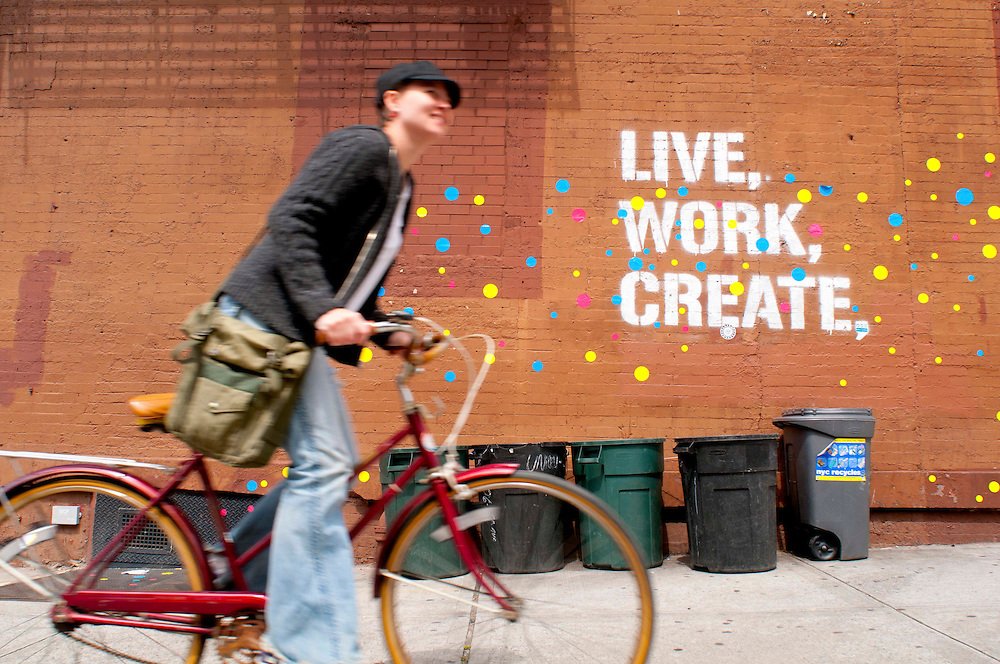 "A Caucasian woman in her late 20s wearing a grey hate, gray sweater, jeans, and an army green bag rides her red bike past a sign that says ""Live. Work. Create."" The sign Is painted in white on the side of a brick building in Brooklyn, NY. It is surrounded by blue, yellow, and pink dots. There are 5 green garbage cans below the sign."