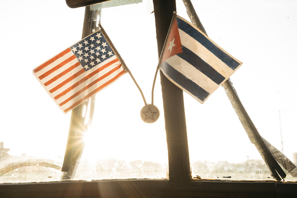 A US flag paired with a Cuban flag hangs on the windshield of the car as Tim Gallagher and Martjan Lammertink make their way to Guantanamo in Eastern Cuba on Jan 28, 2016.