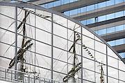 Nederland, Amsterdam, 22 08-2010 SAIL 2010, tall ships in de Amsterdamse IJ-haven. Reflectie van de masten van een van de zeilschepen in de ramen van de gebouwen aan de kade. Publiek kijkt naar de zeilschepen. Het is het grootste publieksevenement van Nederland en een van de grootste maritieme manifestaties ter wereld. Foto: Flip Franssen/Hollandse Hoogte