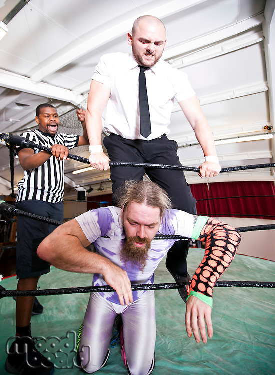 Wrestlers fighting while referee counting during match
