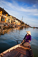A vietnamese woman raws a little boat on the river of Hoi An, Vietnam, Asia. Street of Bach Dang in background