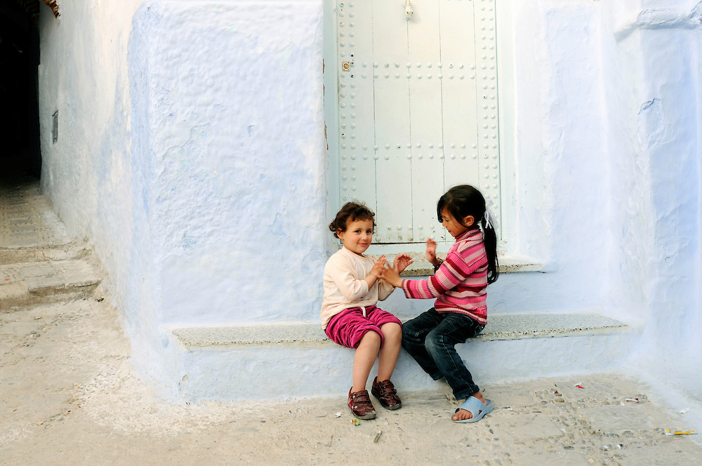 Morocco, Chefchaouen. Girls playing at the blue door.