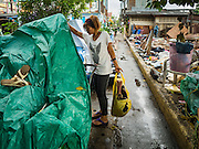 16 NOVEMBER 2015 - BANGKOK, THAILAND:  A woman, one of the last people living in the Wat Kalayanamit neighborhood, packs her belongings. Fifty-four homes around Wat Kalayanamit, a historic Buddhist temple on the Chao Phraya River in the Thonburi section of Bangkok, are being razed and the residents evicted to make way for new development at the temple. The abbot of the temple said he was evicting the residents, who have lived on the temple grounds for generations, because their homes are unsafe and because he wants to improve the temple grounds. The evictions are a part of a Bangkok trend, especially along the Chao Phraya River and BTS light rail lines. Low income people are being evicted from their long time homes to make way for urban renewal.          PHOTO BY JACK KURTZ