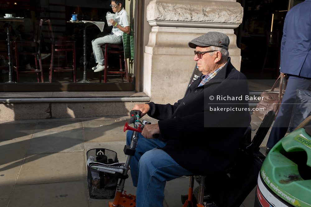 A man in a mobility scooter drives past another sitting in the sunlit cafe window, on 25th October 2018, in Piccadilly, London, England.