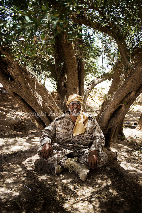 LIBYAN ARAB JAMAHIRIYA, Nalut : Libyan rebel fighter have a sit as he is waiting the order to enter the southwest village of Gazaia as rebels attack forces loyal to Moamer Kadhafi, on July 28, 2011.ALESSIO ROMENZI