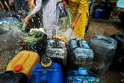 Indian women getting fresh water from a delivery truck, Delhi, India.