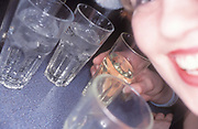 Woman with glasses on a table, in a bar, smilling into the camera, UK 2004
