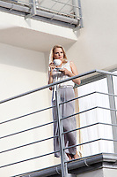 Full length of young businesswoman having coffee at hotel balcony