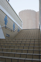 Dubai UAE A businessman ascends a staircase leading to Deira's souqs old fortress architecture.