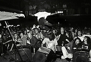 Stage diver launches himself into the crowd from the stage at a rock gig W.Australia 1990's.