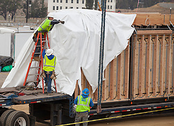 Workers from Blu Homes install parts of a 2300 square foot Breezehouse that will be used as a Design Center located a half mile from their factory on Mare Island in Vallejo, California.  The premium prefab LEED certifiable homes are built with steel frames and hinges that fold during transport and unfold for assembly on the foundation.