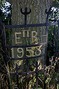 Ironwork celebrating Queen Elizabeth's coronation in 1953, around an oak tree at a remote lane near Irstead in rural Norfolk.