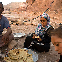 Suleiman and his two daughters eating grilled meat and bread before the arrival of the guests. Suleiman would like to have a boy that could look after him when older. His daughters, once married, will go and live with their husbands'family