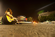 Israel, Tel Aviv, Dizengoff circle at night a young woman plays the guitar