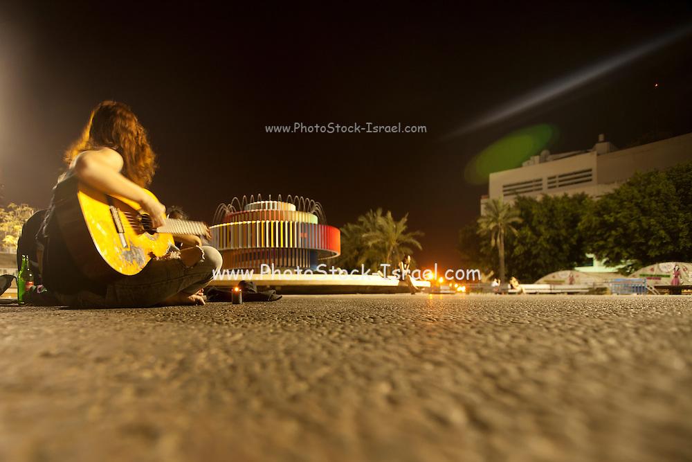 Israel, Tel Aviv, Dizengoff circle at night a young woman plays the guitar