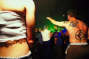 Man with tattooed back dancing at club, UK, 2000