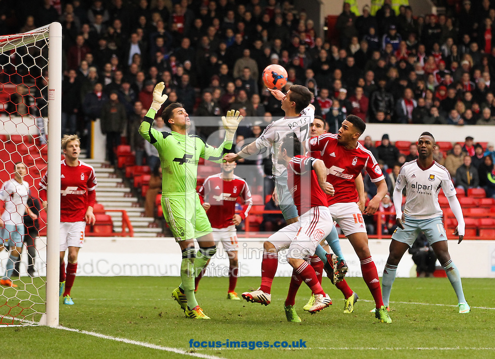 Picture by Tom Smith/Focus Images Ltd 07545141164<br /> 05/01/2014<br /> Dan Potts (centre) of West Ham United tries to get his head on to a cross during the The FA Cup match at the City Ground, Nottingham.