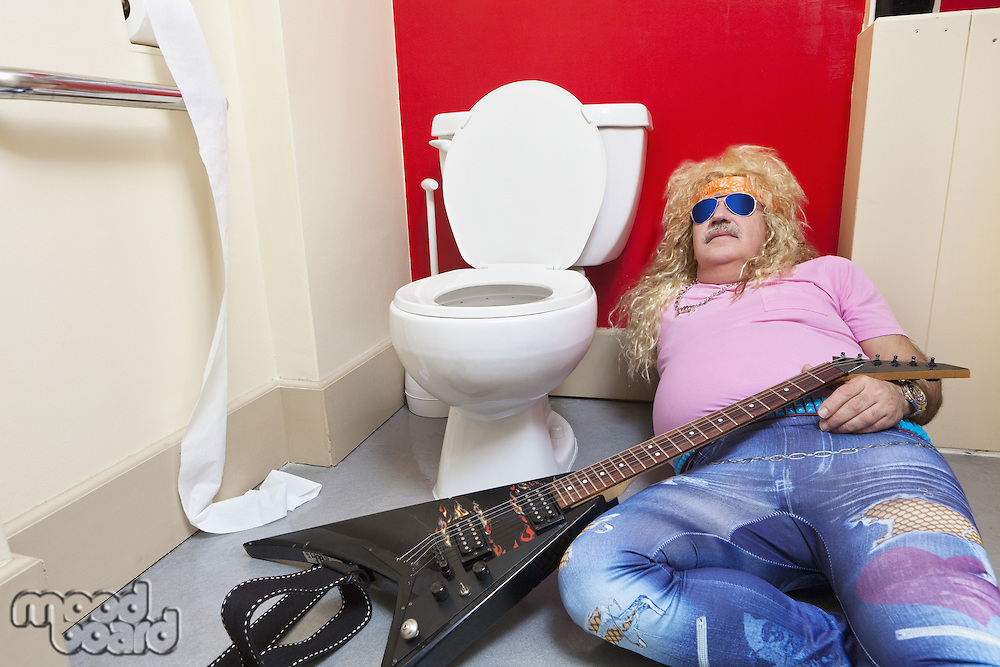 Man lying down in toilet with a guitar