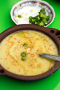 'Bessara' - a Moroccan soup made with dried fava beans, Moulay Idriss, Middle Atlas, Morocco 2016-04-28.<br /><br />Mostly found up north in the Rif and Middle Atlas regions, this subtly flavoured soup is traditionally made with dried, split fava beans, but is even better when fresh beans are in season. The secret to a good bessara is all in the seasoning; it is only lightly spiced and seasoned while cooking, leaving the real flavour to the final touches; a drizzle of olive oil, slithers of raw garlic and sprinkles of freshly ground cumin, paprika and freshly chopped chillis are added before eating.