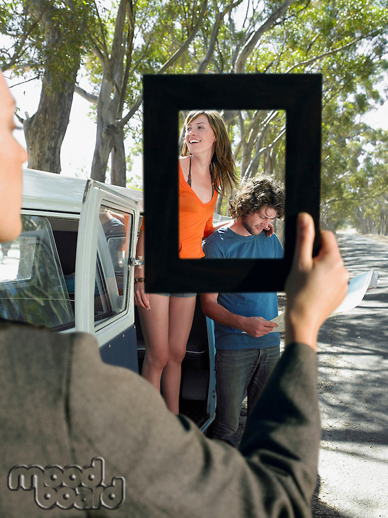 Woman framing a young couple standing by van on a road trip