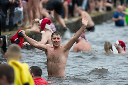 © Licensed to London News Pictures. 25/12/2016. Sutton Coldfield, West Midlands, UK. Due to the mild weather more swimmers than ever took part in the Sutton Coldfield Christmas morning swim. The morning plunge which takes place in Black Root pool has become an annual tradition. Picture shows swimmers in pool. Photo credit: Dave Warren/LNP