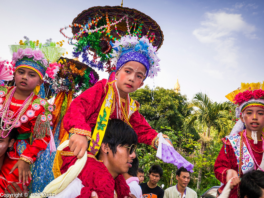 05 APRIL 2013 - CHIANG MAI, THAILAND:      Boys are carried through the grounds of Wat Pa Pao during the Poi Sang Long festival. The Poi Sang Long Festival at Wat Pa Pao in Chiang Mai, Thailand, is an annual festival that marks the ordination of boys in the temple as novice monks. Hundreds of people attend the festival, which is marked by the boys wearing garish makeup and being carried through the temple grounds on the shoulders of older men while musicians play drums and cymbals.    PHOTO BY JACK KURTZ