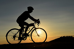 © Licensed to London News Pictures. 01/09/2018. LONDON, UK.  A cyclist atop one of the manmade mounds at Northala Fields near Northolt in west London as the sun sets on the first day of the meteorological autumn.  The forecast is for a few more warm days before temperatures start to cool.  Photo credit: Stephen Chung/LNP