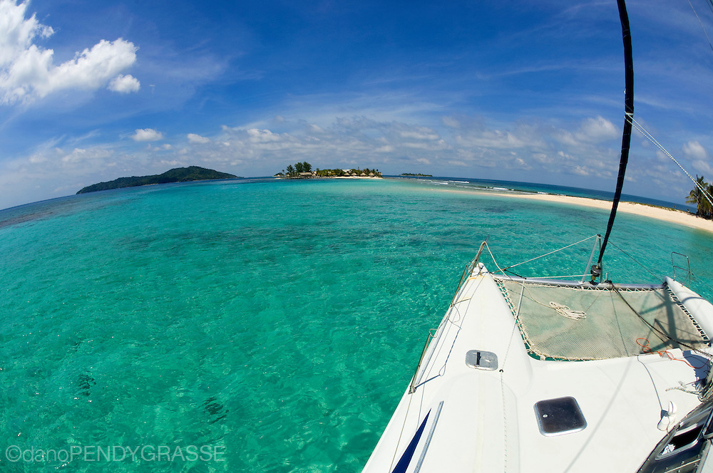 The view of the warm waters around Cayos Cochinos, Honduras from a charter catamaran.