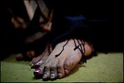 """A detail of the Sweety's feet, a 27 years old transvestite. Sweety wears a shalwar kameez and a black dupatta (traditional scarf).  Sweety is a member of a transvestites' group that live in a same block, built on four floors. Lot of transvestites people are in the same area, often in the same building, where they create a kind community in alternative to the society. Afternoon in Lahore, Pakistan on Tuesday, December 02 2008.....""""Not men nor women"""". Just Hijira, Kusra. Painted lips, Kajal surrounding their eyes and colourful veils..Pakistan is today considered a strongly, foundamentalist as well, islamic country. But under its reputation, above all over the talebans' continuos advancing, stirs a completely extraneous world, a multiethnic mixed society. Transvestites make part of it, despite this would not be admitted by a strict law. Third gender, the Hijira are born as men (often ermaphrodites) or with an ambiguous genital situation, and they have their testicles and penis removed through a - often brutal - surgical operation. The peculiarity is that this operation does not contemplate the reconstruction of a female organ. This is the reason why they are not considered as men nor women, just Hijira. They are often discriminated, persecuted  and taxed with being men prostitutes in the muslim areas. The members of this chast perform dances during celebrations, especially during weddings, since it is anciently believed that an EUNUCO's dance and kiss in the wedding day brings good luck to the couple's fertility...To protect the identities of the recorded subjects names and specific .places are fictionals."""