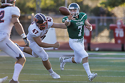 {BLOOMINGTON, IL:  Brandon Bauer flicks the ball to a running back just before Patrick O'Connell makes contact during a college football game between the IWU Titans  and the Wheaton Thunder on September 15 2018 at Wilder Field in Tucci Stadium in Bloomington, IL. (Photo by Alan Look)