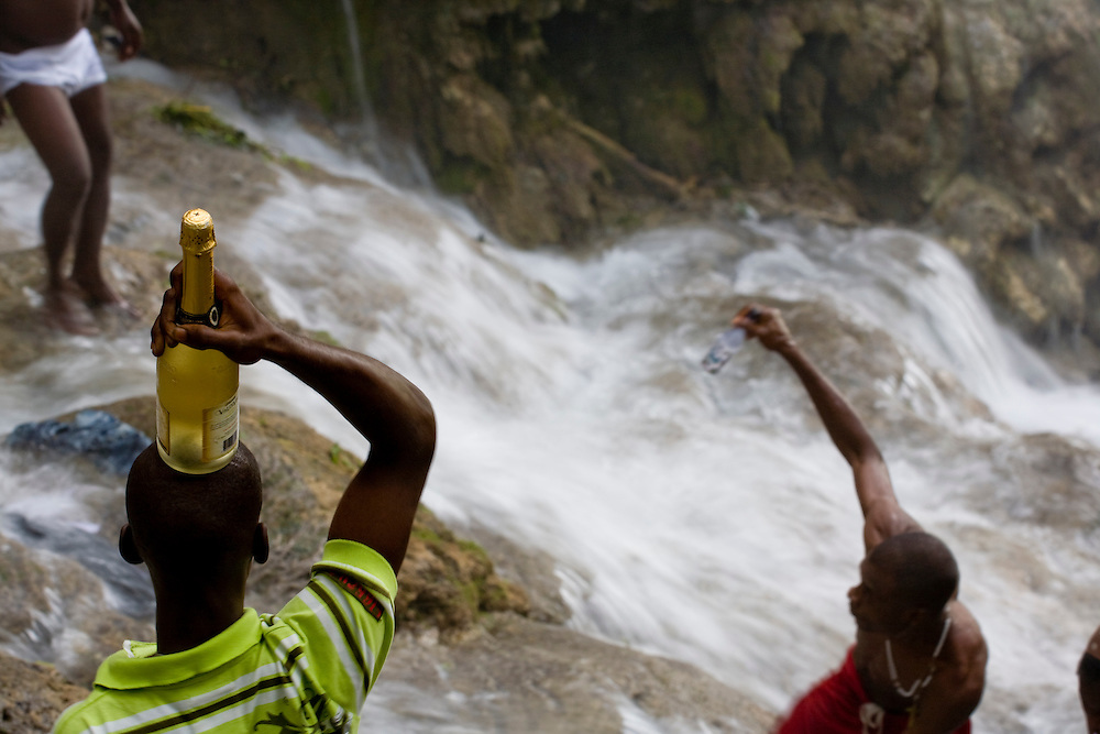A supplicant with a bottle of wine to offer as a sacrifice to invoke the support of the loa, or spirits.                          Haitian pilgrims are gathered at the waterfall at Saut d'Eau on July 16th, the anniversary of the 1983 sighting of the Virgin Mary, alternately identified as the Vodou loa of Erzulie Freda, the Goddess of Love..The waterfall at Saut D'Eau is the site of the largest Vodou and Catholic pilgrimage in Haiti. A second sighting of the Virgin was reported during the American occupation. Each year, thousands of Haitian pilgrims make their way to Saut D'Eau to bathe in the sacred water and revel in the presence of the loa, particularly Erzulie and Damballah the Serpent, father of all life and keeper of spiritual wisdom, who is said to live in the falls. The water is believed to be curative and many women come to Saut d'Eau seeking fertility.    Haitian pilgrims gather at the waterfall at Saut d'Eau on July 16th, the anniversary of the 1983 sighting of the Virgin Mary, alternately identified as the Vodou loa of Erzulie Freda, the Goddess of Love..The waterfall at Saut D'Eau is the site of the largest Vodou and Catholic pilgrimage in Haiti. A second sighting of the Virgin was reported during the American occupation. Each year, thousands of Haitian pilgrims make their way to Saut D'Eau to bathe in the sacred water and revel in the presence of the loa, particularly Erzulie and Damballah the Serpent, father of all life and keeper of spiritual wisdom, who is said to live in the falls. The water is believed to be curative and many women come to Saut d'Eau seeking fertility.                    Haitian pilgrims gather at the waterfall at Saut d'Eau on July 16th, the anniversary of the 1983 sighting of the Virgin Mary, alternately identified as the Vodou loa of Erzulie Freda, the Goddess of Love..The waterfall at Saut D'Eau is the site of the largest Vodou and Catholic pilgrimage in Haiti. A second sighting of the Virgin was reported during the American occ