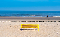 Portobello, Scotland, UK. 25 April 2020. Views of people outdoors on Saturday afternoon on the beach and promenade at Portobello, Edinburgh. Good weather has brought more people outdoors walking and cycling. Police are patrolling in vehicles but not stopping because most people seem to be observing social distancing.  Solitary yellow bench on an empty beach.  Iain Masterton/Alamy Live News